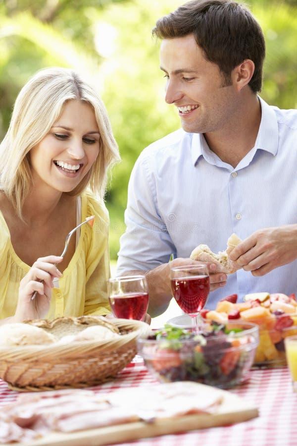 Pares que disfrutan de la comida al aire libre junto fotos de archivo