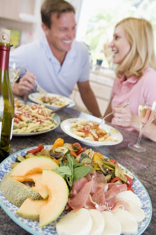 Pares que disfrutan de la comida, mealtime junto fotos de archivo libres de regalías