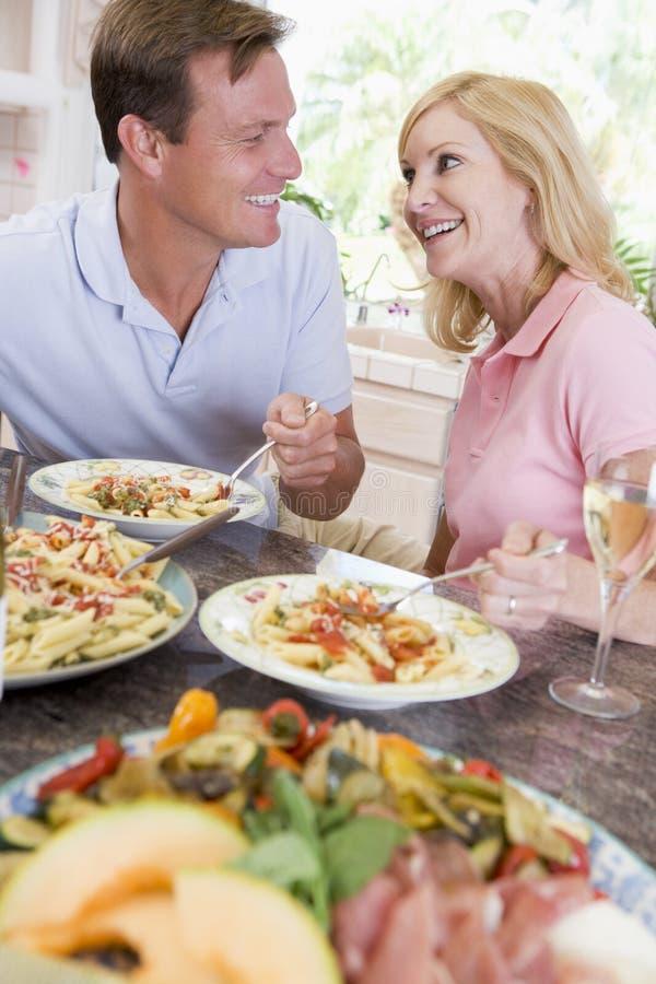 Pares que disfrutan de la comida, mealtime junto fotografía de archivo