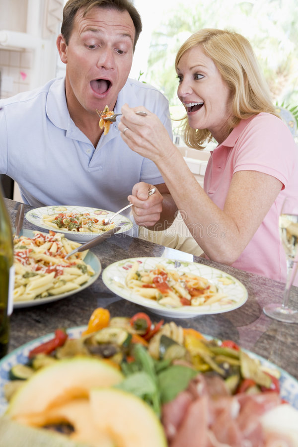 Pares que disfrutan de la comida, mealtime junto imagen de archivo libre de regalías