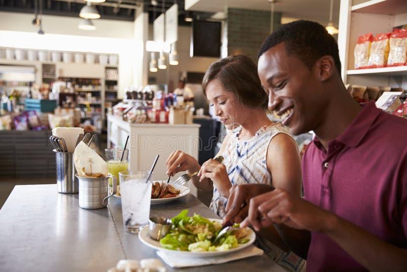 Pares que disfrutan de la fecha del almuerzo en restaurante de la charcutería imágenes de archivo libres de regalías