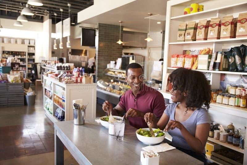 Pares que disfrutan de la fecha del almuerzo en restaurante de la charcutería imagenes de archivo