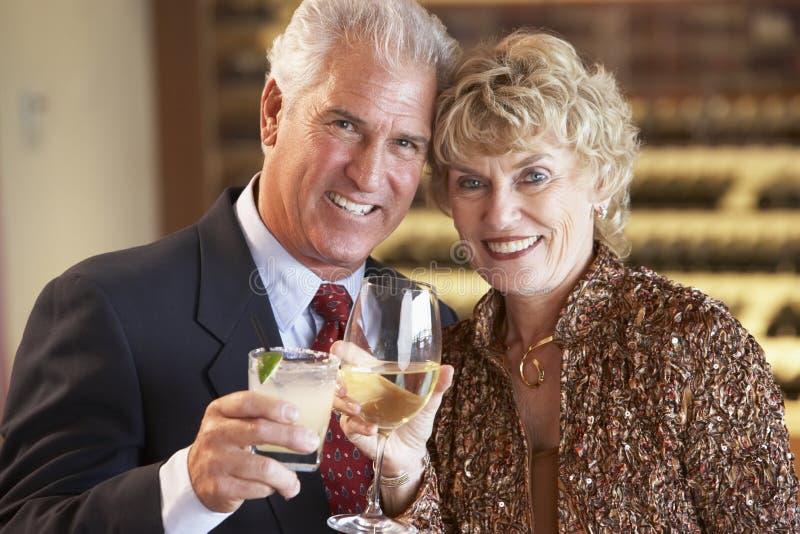 Pares que disfrutan de una bebida en una barra junto foto de archivo