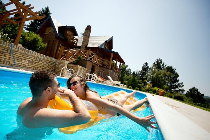 Pares que disfrutan de verano en piscina fotos de archivo