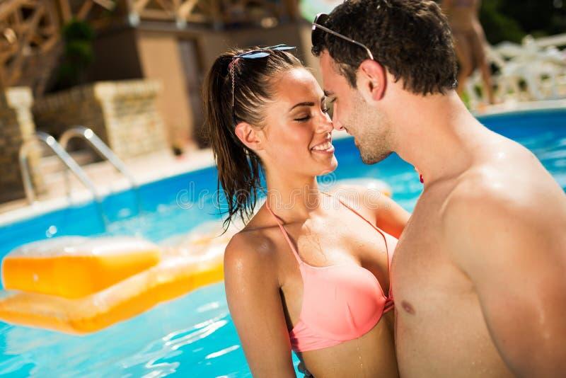 Pares que disfrutan de verano en piscina imágenes de archivo libres de regalías