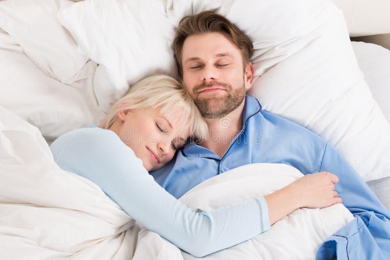 Pares que dormem junto na cama foto de stock