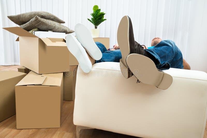 Pares que dormem no sofá na casa nova imagens de stock royalty free