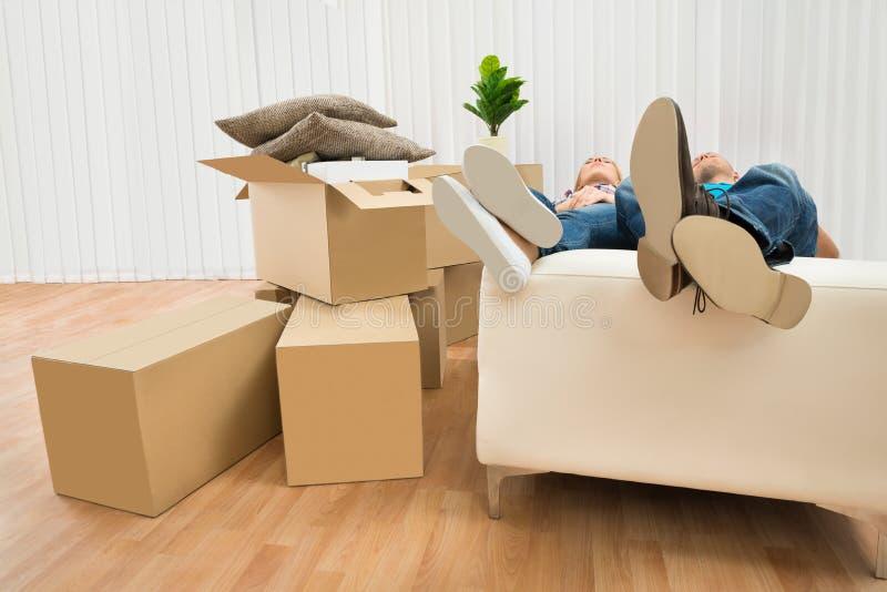 Pares que dormem no sofá na casa nova fotografia de stock
