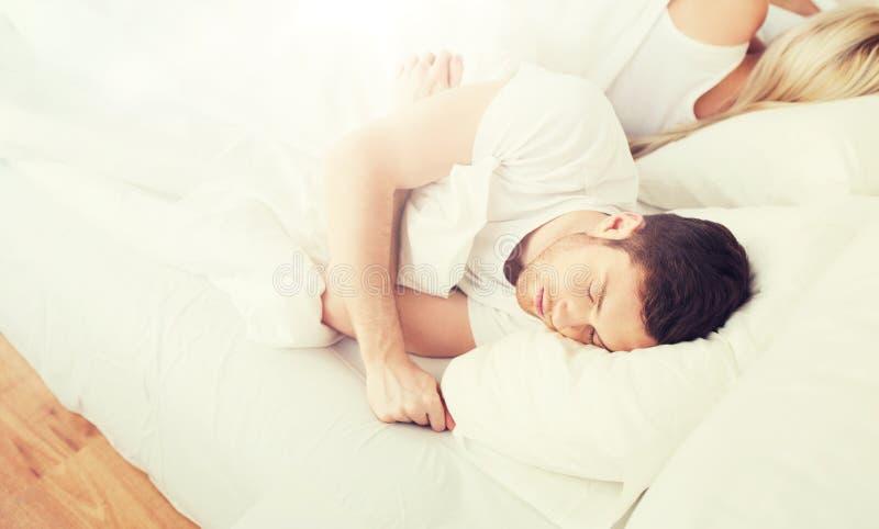 Pares que duermen en cama en casa fotografía de archivo libre de regalías
