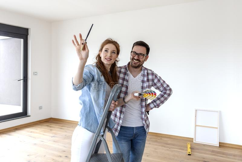 Pares que eligen los colores para el apartamento de la pintura imágenes de archivo libres de regalías