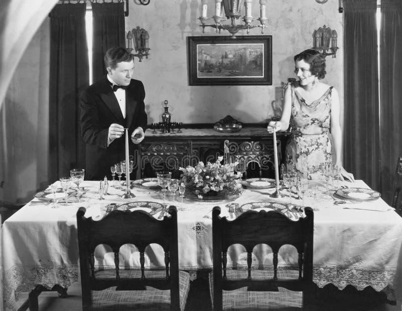 Pares que encienden velas en el sistema de la tabla para la cena (todas las personas representadas no son vivas más largo y ningú imagen de archivo