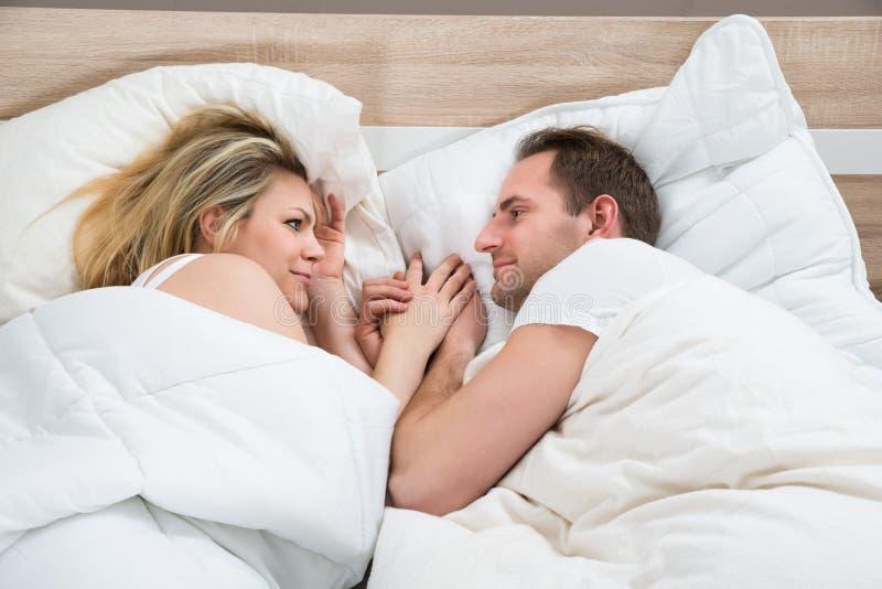 Pares que encontram-se na cama fotografia de stock royalty free