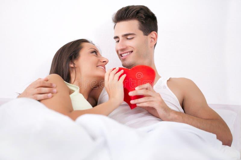 Pares que encontram-se no coração do Valentim da cama imagem de stock royalty free