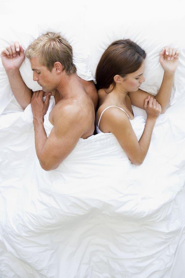 Pares que encontram-se no sono da cama fotos de stock royalty free