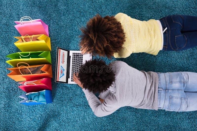 Pares que encontram-se no tapete que compra em linha no portátil foto de stock