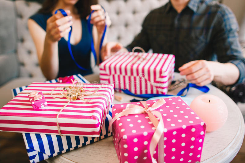 Pares que envuelven los regalos para la familia y los amigos imagen de archivo