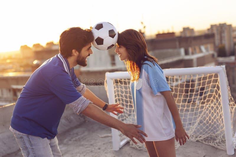 Pares que equilibran con un fútbol entre sus cabezas foto de archivo