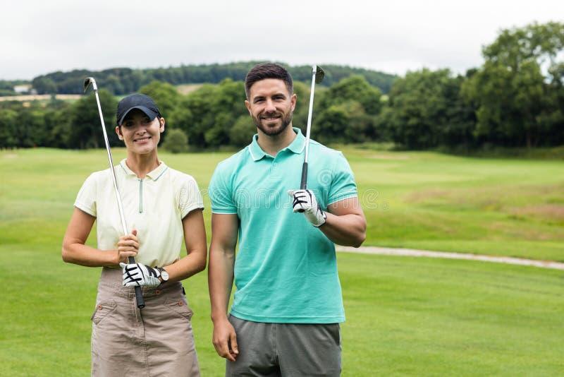 Pares que estão com o clube de golfe no campo de golfe fotografia de stock