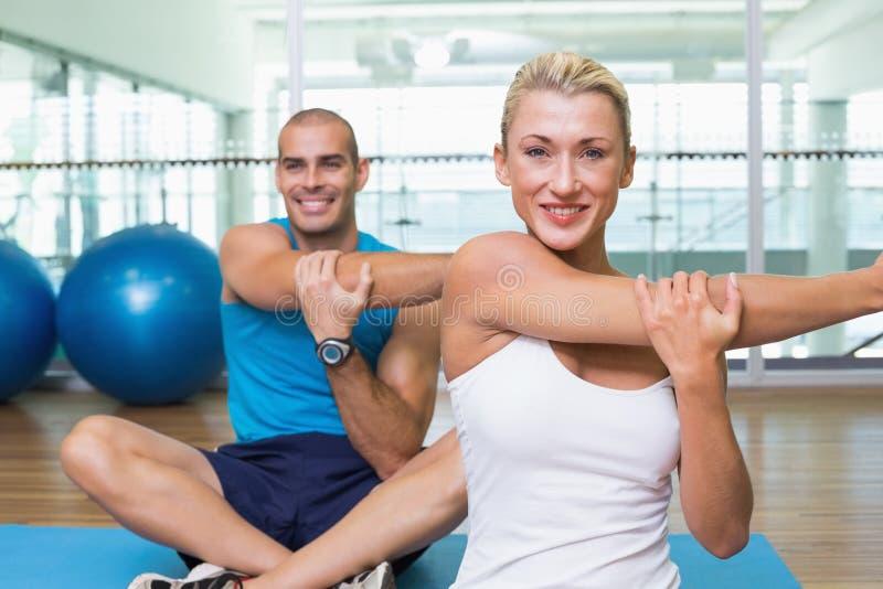 Pares que esticam as mãos na classe da ioga imagens de stock royalty free