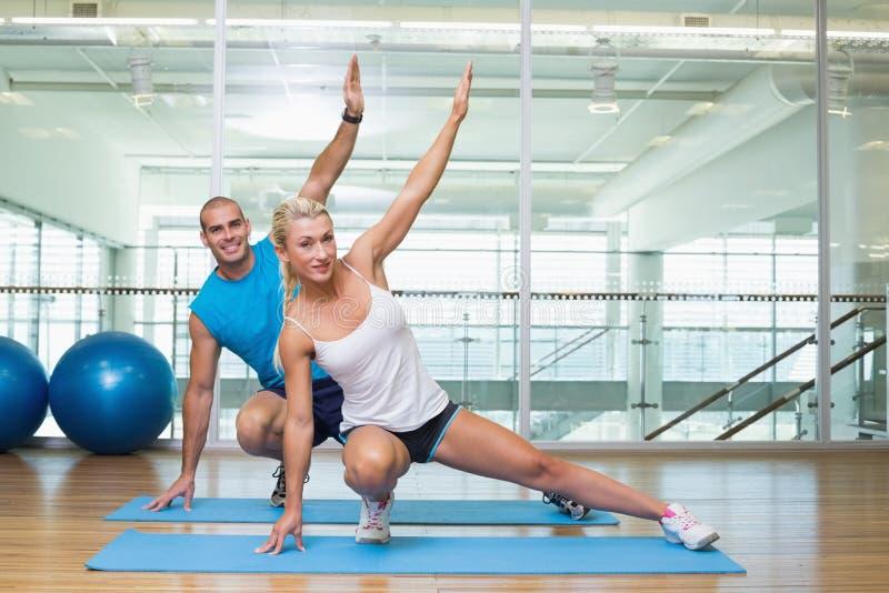 Pares que esticam as mãos na classe da ioga imagem de stock