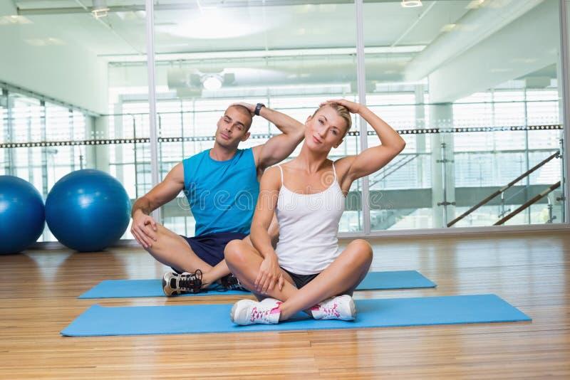 Pares que esticam os pescoços na classe da ioga imagens de stock