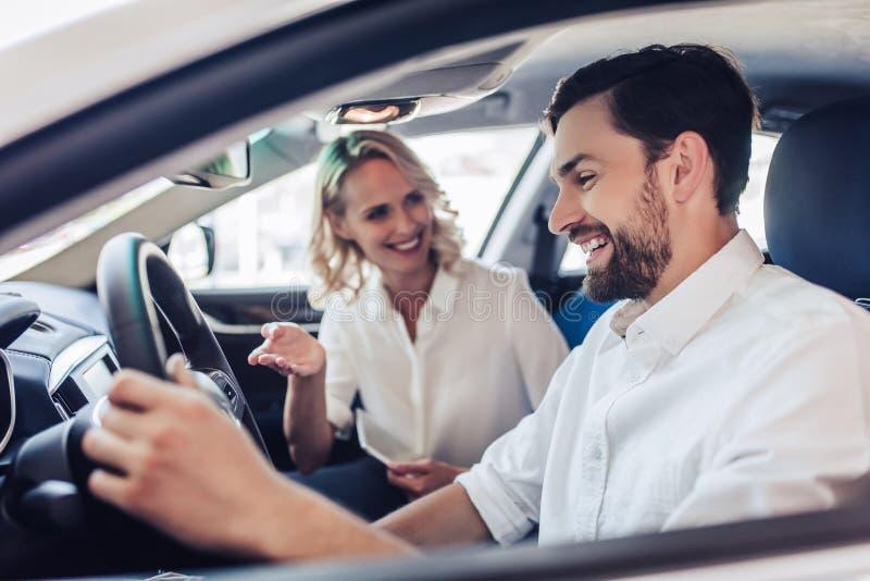 Pares que falam ao conduzir um carro fotografia de stock royalty free