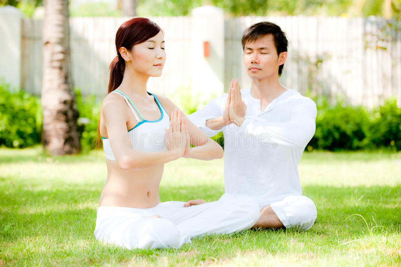 Pares que fazem a ioga foto de stock