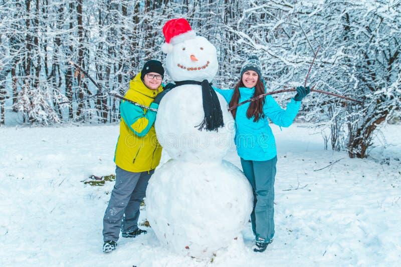 Pares que fazem o boneco de neve no dia de inverno congelado imagens de stock royalty free
