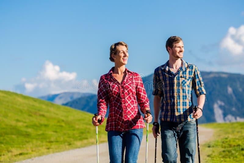 Pares que fazem o exercício de passeio do nordic nas montanhas fotos de stock