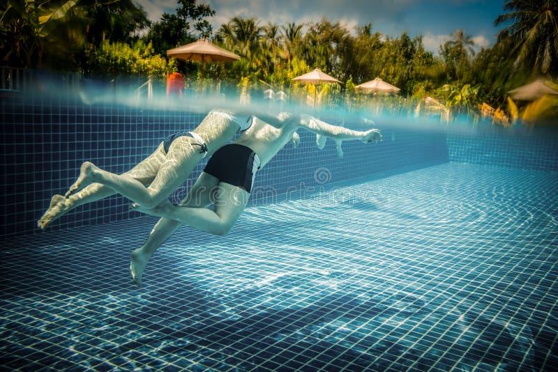 Pares que flotan en la piscina el día de fiesta imagen de archivo libre de regalías