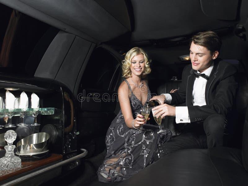 Pares que gozan de Champagne In Limousine fotografía de archivo