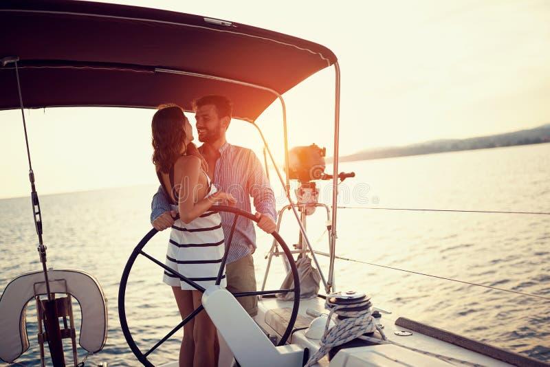 Pares que gozan en el barco de lujo en la puesta del sol fotografía de archivo