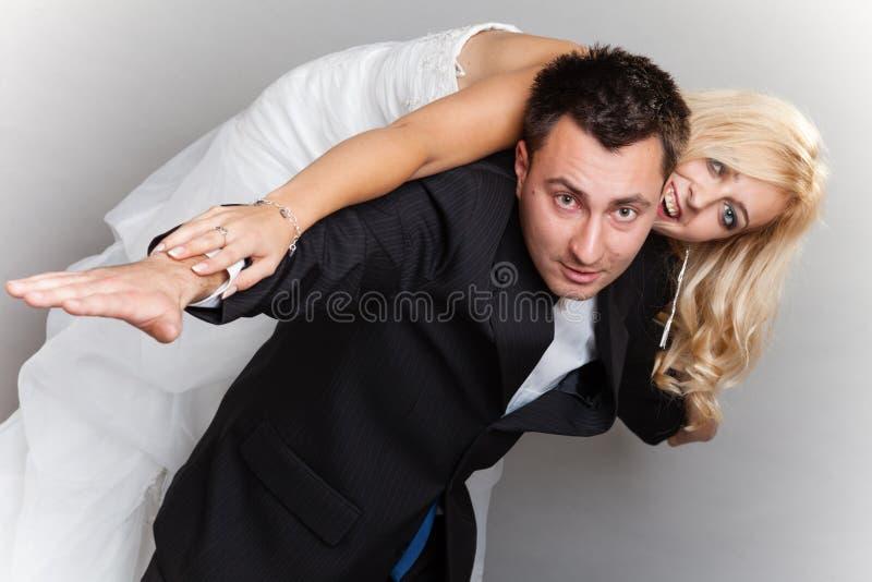 Pares que gozan, mujer de la boda en la parte posterior del varón imagen de archivo libre de regalías