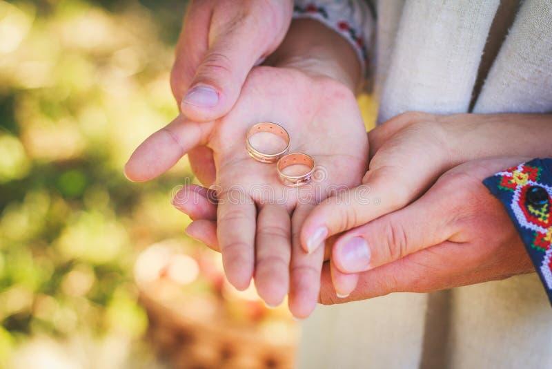 Pares que guardam as alianças de casamento em suas mãos imagens de stock