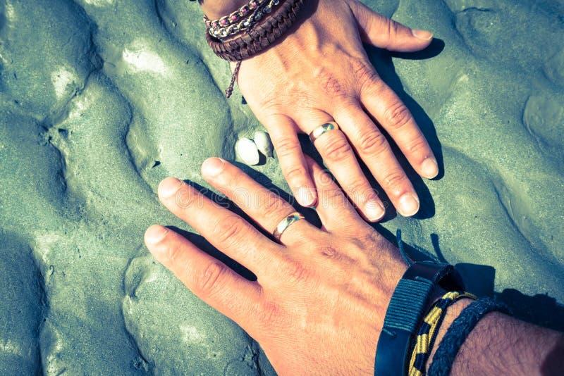 Pares que guardam as mãos junto com seu mostrar dos anéis fotografia de stock