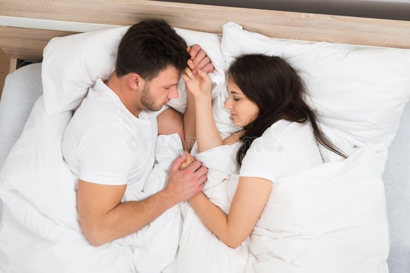 Pares que guardam as mãos que dormem na cama imagem de stock