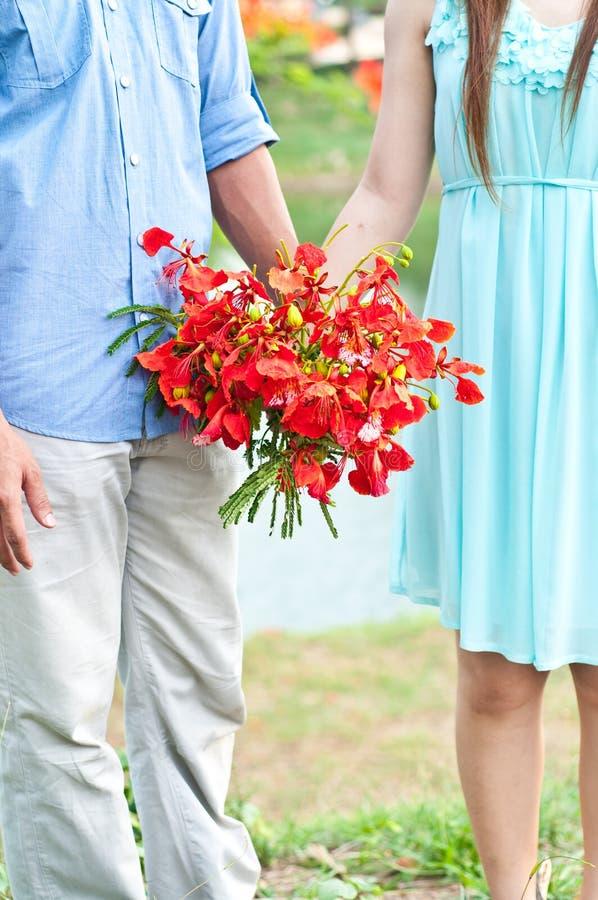 Pares que guardam flores vermelhas fotografia de stock