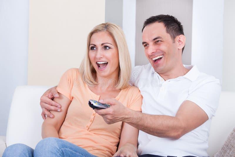 Pares que guardam a televisão remota e olhando foto de stock royalty free