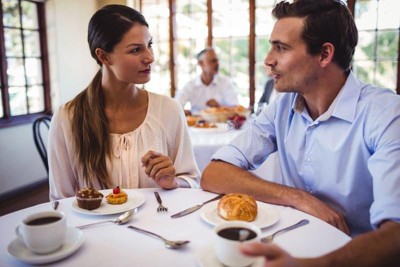 Pares que hablan con uno a en restaurante fotografía de archivo
