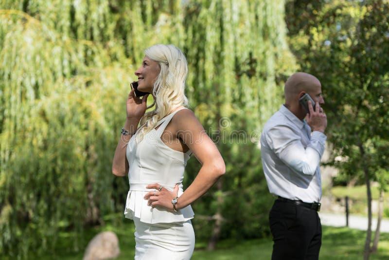 Pares que hablan en el teléfono móvil o elegante El hombre y la mujer hablan con el teléfono La gente joven utiliza el teléfono m fotos de archivo