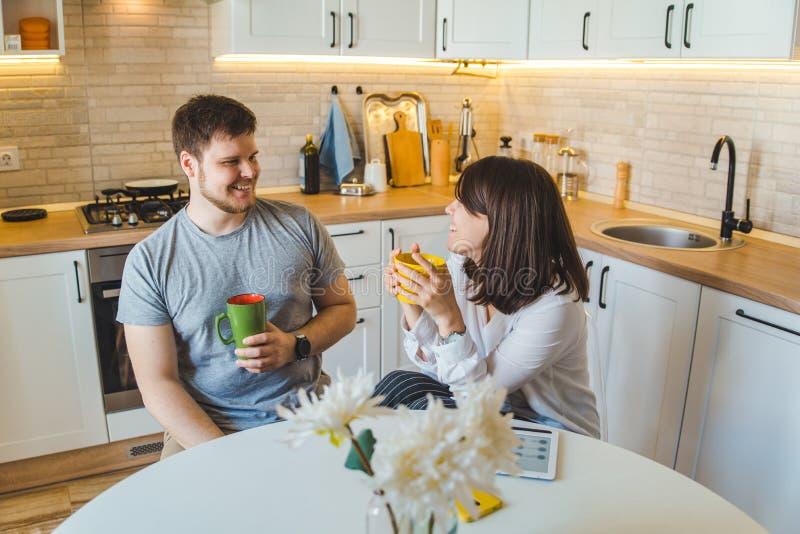 Pares que hablan en la cocina en el té de consumición de la mañana fotos de archivo libres de regalías