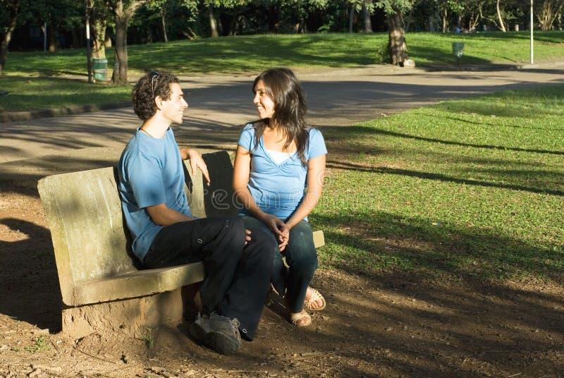 Pares que hablan en un banco de parque - horizontal fotografía de archivo