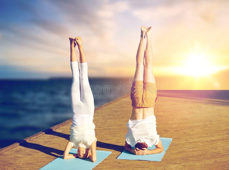 Pares que hacen el headstand de la yoga en la estera al aire libre fotos de archivo libres de regalías