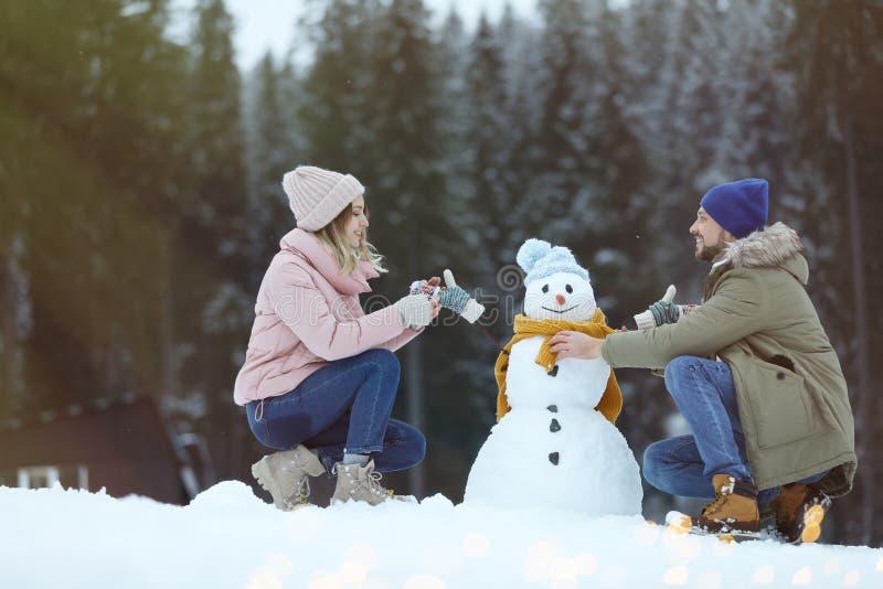 Pares que hacen el muñeco de nieve cerca de bosque imagen de archivo