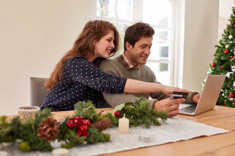 Pares que hacen las compras en línea para la Navidad fotografía de archivo libre de regalías