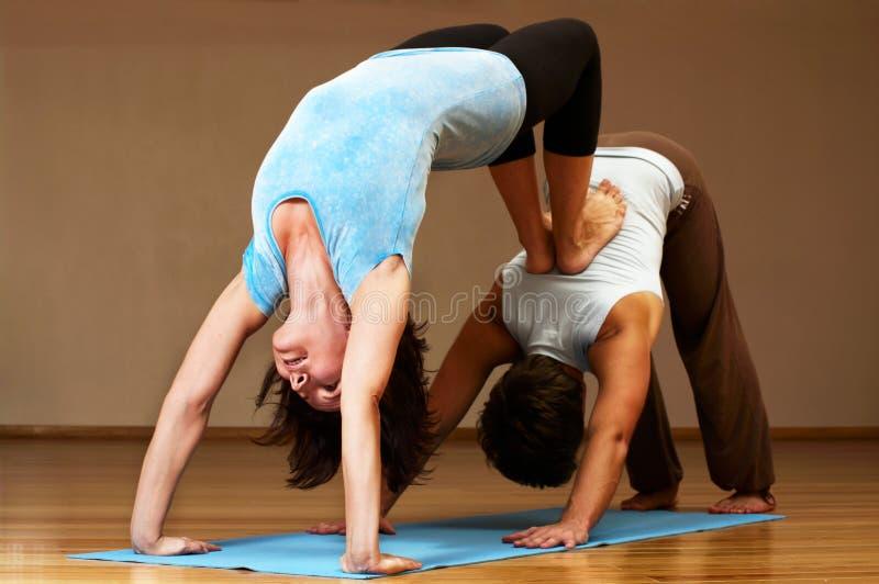 Pares que hacen práctica de la yoga fotografía de archivo libre de regalías