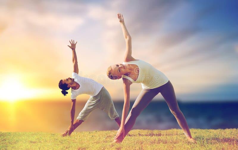 Pares que hacen que yoga el triángulo presenta al aire libre fotos de archivo