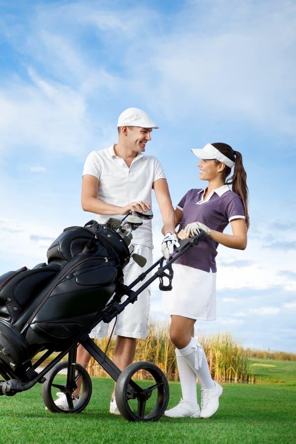 Pares que jogam o golfe em um dia ensolarado foto de stock royalty free
