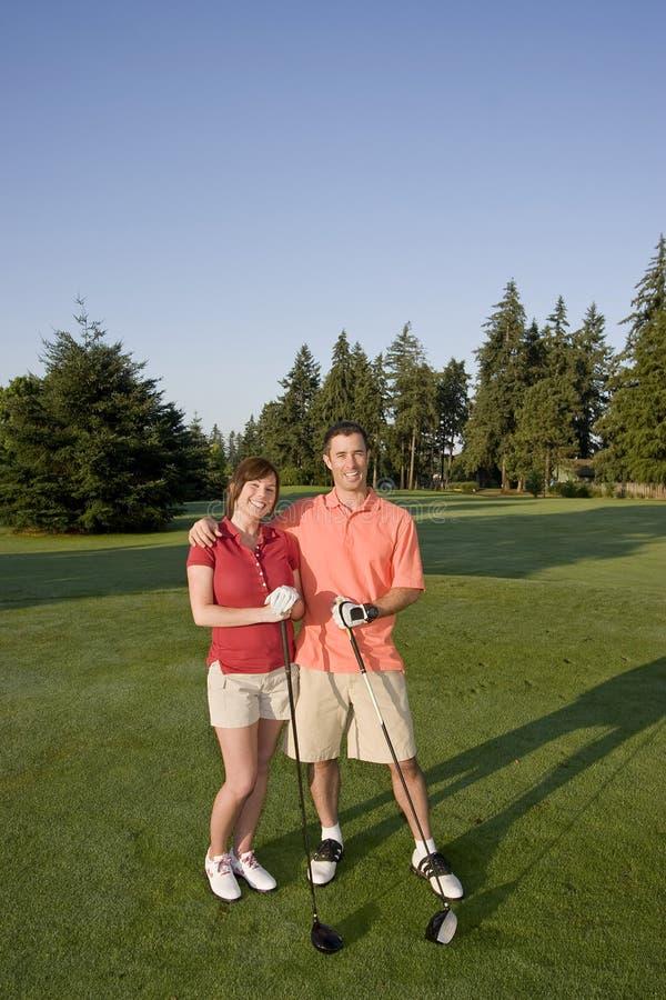 Pares que jogam o golfe no curso - vertical fotos de stock royalty free