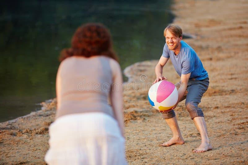 Pares que jogam o voleibol com bola de praia fotografia de stock royalty free